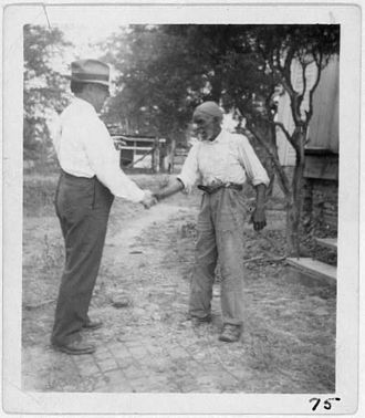 "Blues - John Lomax (left) shaking hands with musician ""Uncle"" Rich Brown in Sumterville, Alabama"