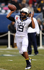 "An American football player in a white uniform with ""Navy"" across the front throws a ball to a receiver out of frame."