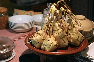 Ketupat - Unopened bunch of cooked ketupat on a plate.