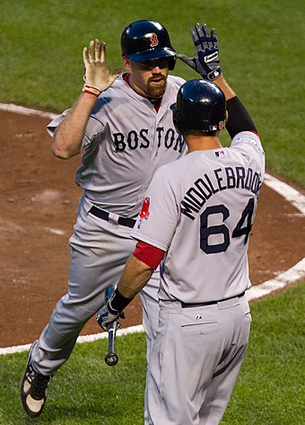 Youkilis being congratulated by Will Middlebrooks Kevin Youkilis , Will Middlebrooks (7253775924).jpg