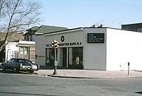 A bank building on the corner of a city street. A car can be seen parked out front and a traffic light is located on the sidewalk in front of the building. Other buildings can be seen in the background.