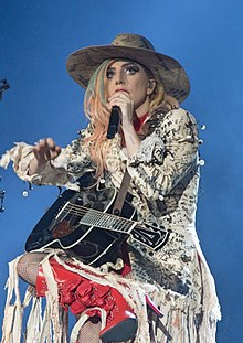 Lady Gaga sitting in a chair with a guitar, wearing a wide-brim hat and a white blazer.