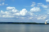 A bright blue lake with a line of trees along the horizon, interrupted only by a cooling tower for the nuclear power plant in Russellville, and puffy white clouds in the blue sky