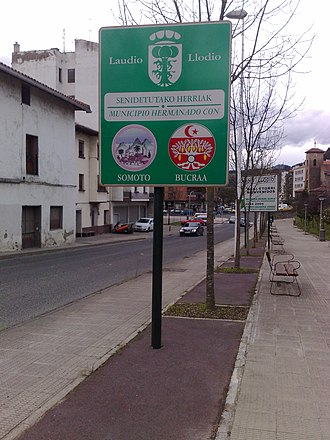 Bou Craa - Sign in Llodio showing the coat of arms of its twin town Bou Craa (Bucraa).