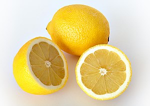 Two lemons, one whole and one sliced in half
