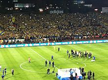 A stand full of football supporters clad in yellow and blue, beside a pitch.