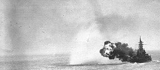 "USS Massachusetts (BB-59) - Massachusetts shelling Kamaishi, Honshū, Japan on 14 July 1945. Outbound projectiles of a full broadside of her 16"" guns are visible in upper left of photo."
