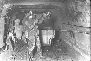 Miners dust the mine walls