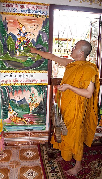 Sang Sinxay - A monk holding bundles of Sang Sinxay palm-leaf manuscripts while pointing to a painting of Sinxay.