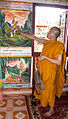 Monk holding bundles of Sinxay palm leaf manuscripts while pointing to a painting of Sinxay within the sim.jpg