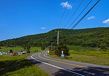 "A two-lane paved road winding through countryside from just right of the camera, down the center of the frame, towards a hill covered with green trees under a blue sky with some small clouds in it. On the far side of the road there is a sign with the number 22 on it; below it is a white on blue sign with ""Be Prepared to Stop"" on it in capital letters. Telephone wires enter the image from top left, connecting to a wooden pole at the center"