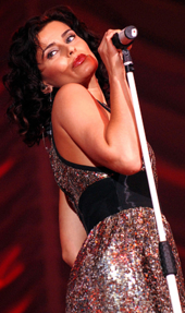 A young woman with dark hair and red lipstick, wearing a sparkling silver dress and a wide black belt, singing into a microphone, looking over her right shoulder.