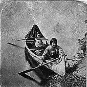 Three or four dark haired women near the shore in a canoe