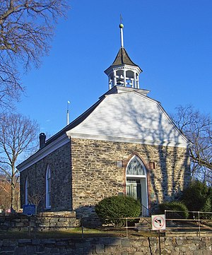 A small stone building with a bell-shaped roof and upper section sided in wood seen from slightly below and to its right. There is a wooden bell tower on top with a weathervane. All the windows have rounded tops that end in points.