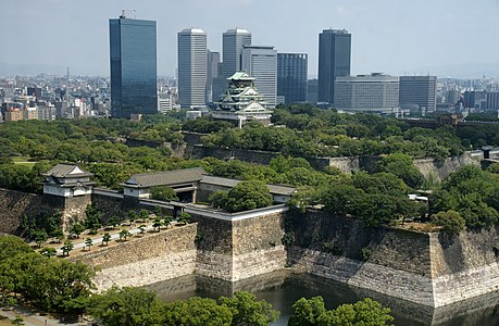 Osaka Castle in Chuo-ku, Osaka, Osaka prefecture, Japan. The main building has been changed, damaged, and repaired multiple times since the original major construction on the site in 1496. The main building is built on two platforms with walls and moats outside of each platform. Modern skyscraper buildings are visible in the background.