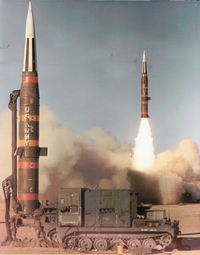 missile erect and prepared for launch while missile is launching in background