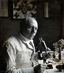Peter (?) Muhlens; seated, with a microscope. Photograph, Wellcome V0028885.jpg