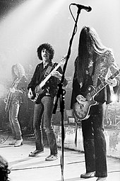 Three members of the band Thin Lizzy are shown onstage. From left to right are a guitarist, bass player, and another electric guitarist. Both electric guitarists have long hair.