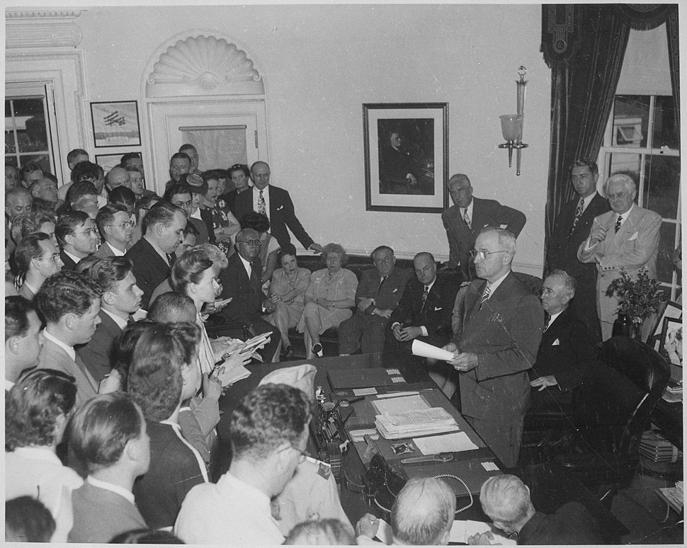 Photograph of President Truman in the Oval Office, reading the announcement of Japan's surrender to assembled... - NARA - 199171