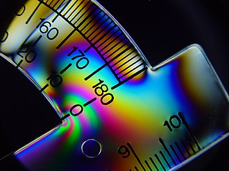 Augustin-Jean Fresnel - Chromatic polarization in a plastic protractor, caused by stress-induced birefringence.