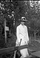 Porträtt av en kvinna i i vit dräkt och hatt vid en bänk - Nordiska Museet - NMA.0057186.jpg