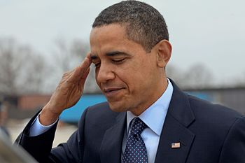 Barack Obama in a dark blue suit looking down slightly, saluting.