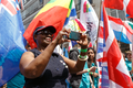 Pride in London 2016 - Woman taking a selfie in front of flag bearers.png