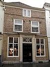 foto van Huis met lijstgevel in schoon werk, ingang met kroonlijst op geblokte pilasters en jaarankers 1590