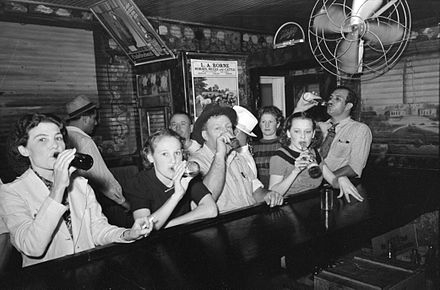 Men and women drinking beer at a bar in Raceland, Louisiana, September 1938. Pre-Prohibition saloons were mostly male establishments; post-Prohibition bars catered to both males and females. Raceland Louisiana Beer Drinkers Russell Lee.jpg