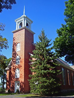 A brick building with a pine tree in front and a tower with white cupola