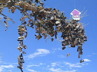 """Tavar Zawacki - A site-specific wooden arrow mobile that reads """"shoe/tree"""" hung from a tree full of shoes. Nevada, U.S.A. 2004"""