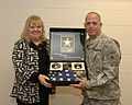 Retired U.S. Army Reserve and former Michigan Army National Guard Capt. Teresa Dobie, receives a retirement flag and pin from Michigan Volunteer Defense Force member, Chief Warrant Officer 3 James Jones.jpg