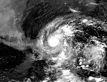 A black and white image of a tropical cyclone. A small eye is visible.