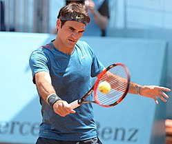 A tennis player holds a racket in his hand