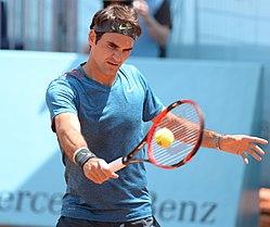 Теннисист держит в руке ракетку