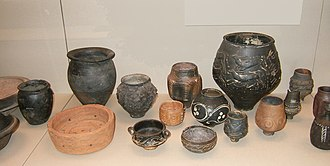 Ancient Roman pottery -  A selection of pottery found in Roman Britain. The assemblage includes Black-burnished ware jars, a Rusticated Ware jar, a Central Gaulish Colour-Coated Ware beaker, Trier Black-slipped Ware with white trailed decoration,  Nene Valley Colour Coated Ware, a coarse ware cheese press and other fine wares.