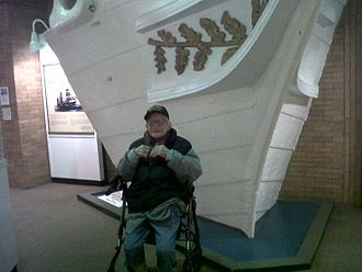 USS Michigan (1843) - Sam Tanenbaum in December, 2013 at age 93 sitting next to the prow of the USS Wolverine which he had donated to the city of Erie PA in 1949