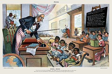 "Caricature by Louis Dalrymple showing Uncle Sam lecturing four children labeled Philippines, Hawaii, Puerto Rico and Cuba, in front of children holding books labeled with various U.S. states. A black boy is washing windows, a Native American sits separate from the class, and a Chinese boy is outside the door. The caption reads: ""School Begins. Uncle Sam (to his new class in Civilization): Now, children, you've got to learn these lessons whether you want to or not! But just take a look at the class ahead of you, and remember that, in a little while, you will feel as glad to be here as they are!"" School Begins (Puck Magazine 1-25-1899).jpg"