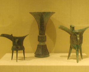 Chinese ritual bronzes - Two Jué on either side of a Gū, all from the Shang dynasty