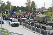 large group of migrants moving along a road, being directed by the army and police