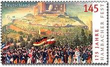 Le timbre reprend le tableau précédent concernant la fête de Hambach, en couleur cette fois. D'autres drapeaux se trouvent à côté de celui allemand.