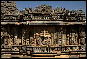 "Bucesvara Temple, Koravangala - Outer wall relief articulation at Bucesvara Temple is of the ""old style""; eaves below superstructure, wall images below decorative miniature towers, five mouldings at the base"