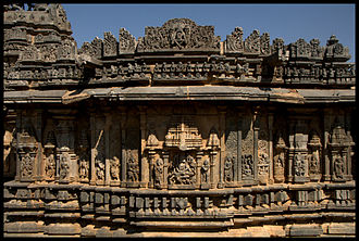"""Bucesvara Temple, Koravangala - Outer wall relief articulation at Bucesvara Temple is of the """"old style""""; eaves below superstructure, wall images below decorative miniature towers, five mouldings at the base"""