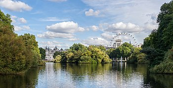 Photograph looking east over St. James's Park Lake from the Blue Bridge, with the London Eye and parks of White Hall visible above the trees in the distance.