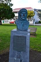 A bronze bust of a man wearing a balaclava, the bust on a plinth in a park area with a backdrop of a park bench and buildings in the far distance