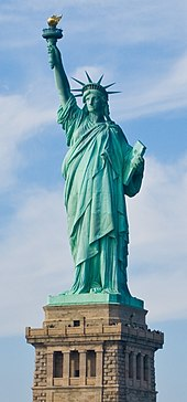 The Statue of Liberty, a large teal bronze sculpture on a stone pedestal