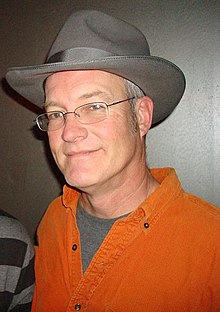 A middle-aged Caucasian man wearing spectacles, a gray fedora and an orange shirt smiles for a camera.