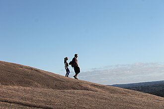 Fredericksburg, Texas - A couple strolling down from the top of Enchanted Rock