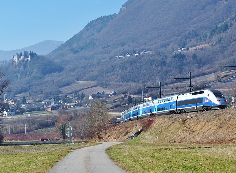 Sight of French TGV on winter service journey n°990 from Bourg-Saint-Maurice in the Alps to Brest in Brittany, passing below the Arclusaz mountain near Miolans castle, in Savoie.
