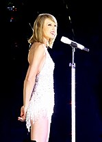 Taylor Swift performing wearing a white outfit.
